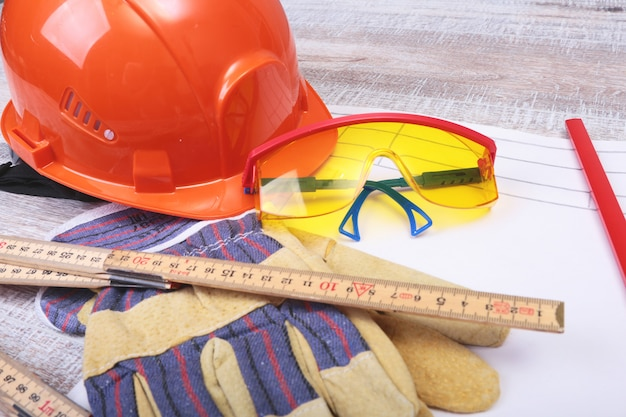 Capacete laranja, óculos de segurança, luvas e fita métrica