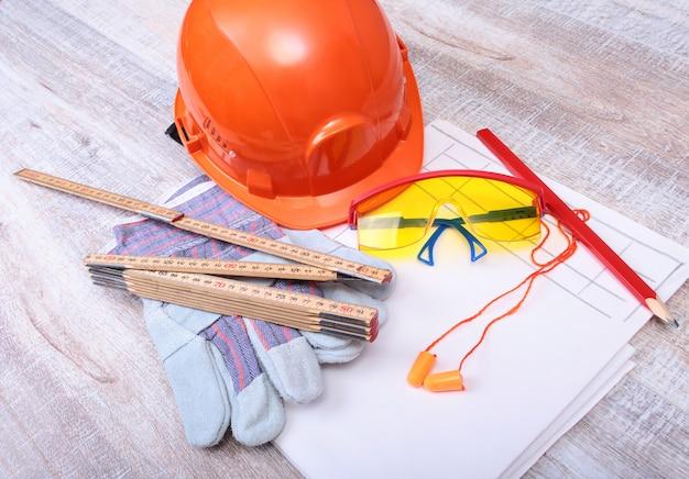 Capacete laranja, tampão para os ouvidos, óculos de segurança e luvas para o trabalho. tampão para reduzir o ruído