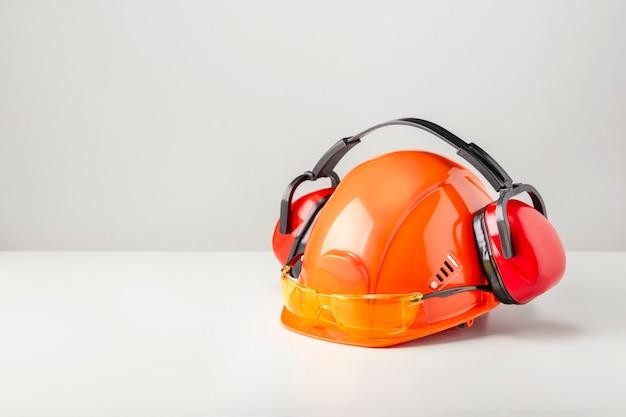 Capacete protetor com fones de ouvido e óculos na superfície cinza com espaço de cópia.