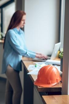 Capacete protetor no peitoril da janela e mulher trabalhando no laptop