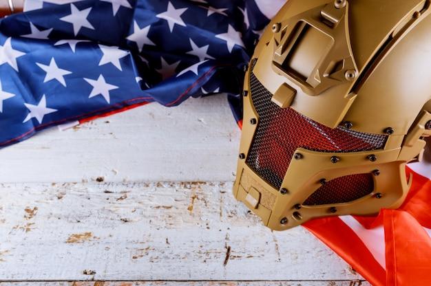 Capacetes militares e bandeira americana em veteranos ou dia memorial