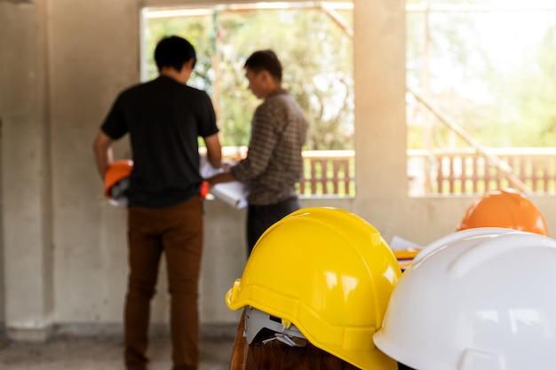 Capacetes na mesa na frente do engenheiro ou arquiteto discutindo no canteiro de obras