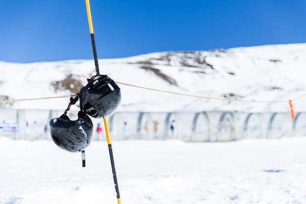 Capacetes pendurados na montanha da neve