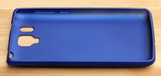 Capas traseiras do smartphone azul em um fundo de madeira
