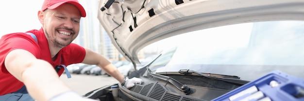 Capataz abrindo o capô do carro e tirando a ferramenta de metal da mala