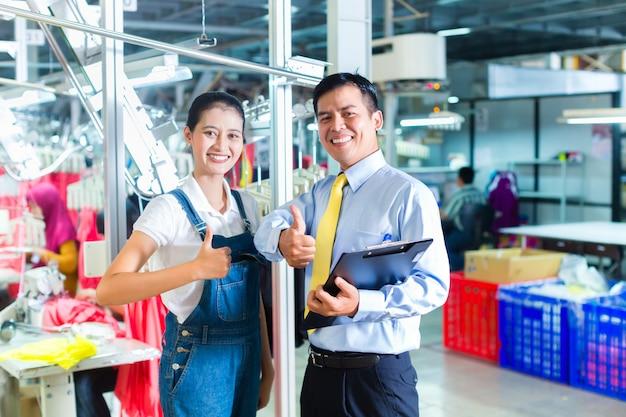 Capataz asiático na fábrica têxtil, dando treinamento