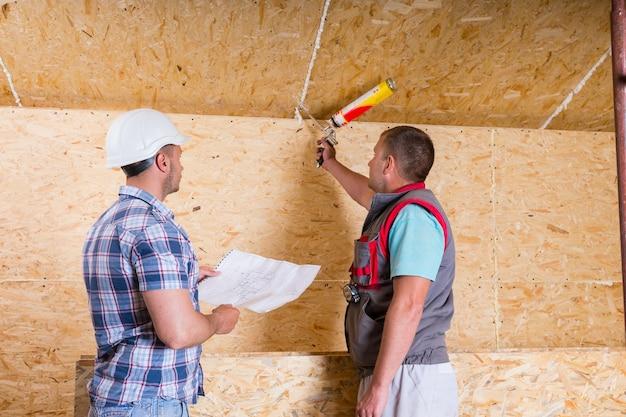 Capataz de obra usando capacete branco segurando plantas e observando trabalhador aplicando calafetagem em teto de madeira inacabado