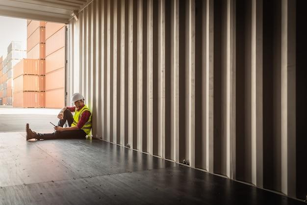 Capataz deprimido e experimentado, sentado na caixa de transporte de contêineres