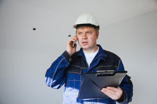 Capataz do construtor com um capacete branco em uma construção interna, conceito de renovação plana, capataz profissional no trabalho usando smartphone