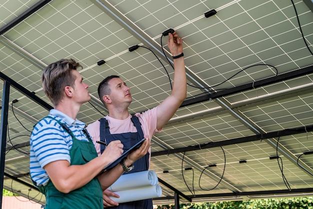 Capataz e engenheiro trabalham na restauração e inspeção de painéis solares. conceito de energia alternativa renovável verde