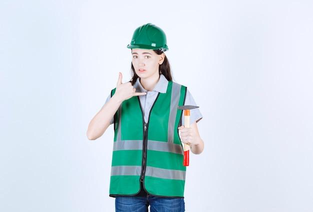 Capataz fazendo um sinal de chamada enquanto segura o martelo em frente à parede cinza
