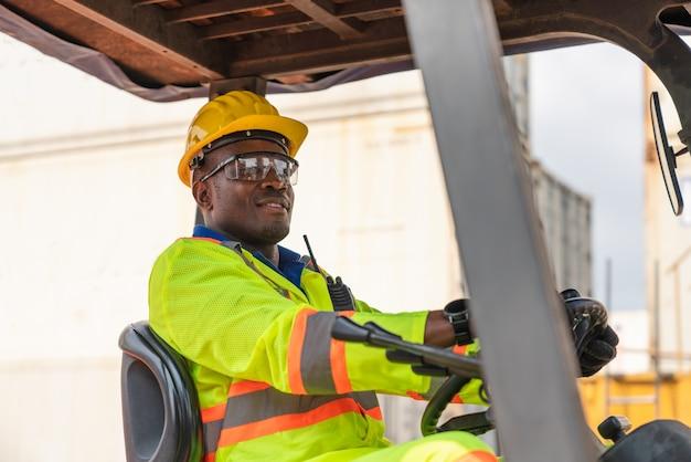 Capataz masculino usar óculos de segurança e capacete amarelo, dirigindo uma empilhadeira no transporte de contêineres