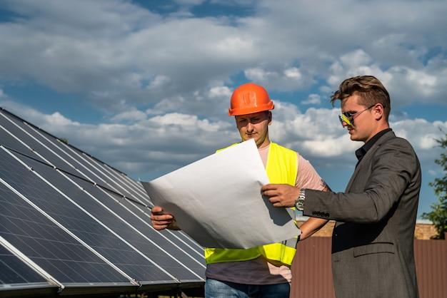 Capataz mostrando empresário de detalhes fotovoltaicos na estação de energia solar. energia verde