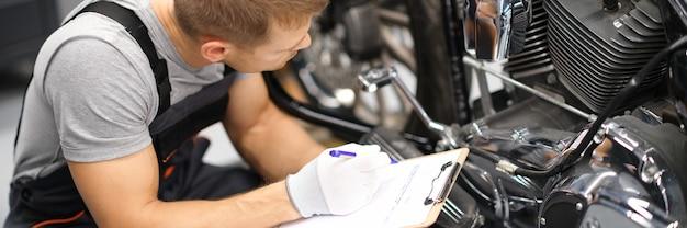 Capataz no centro de reparos de serviço diagnostica peças em motocicletas