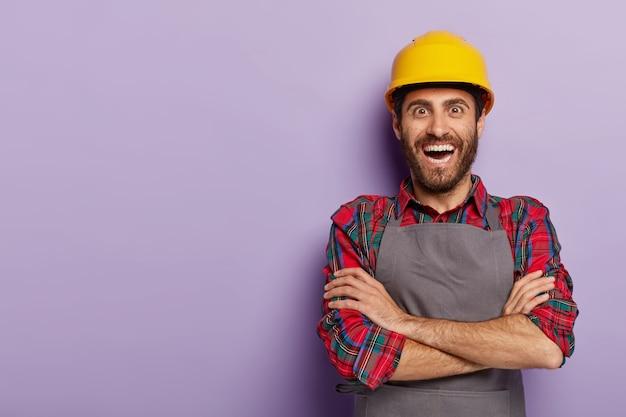 Capataz positivo e feliz em vestuário de trabalho, mantém os braços cruzados, usa capacete amarelo