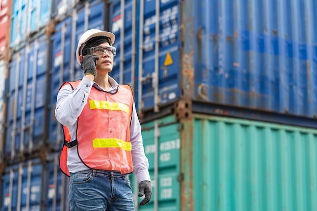 Capataz usando smartphone para ligar para produtos de remessa por cheque no navio de carga de carga no transporte de contêineres