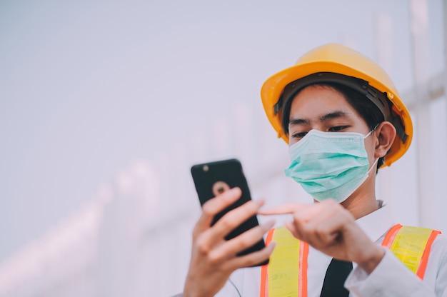Capataz usando telefone móvel esperto na construção do local