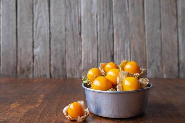 Cape gooseberry fruit em uma tigela sobre uma mesa de madeira