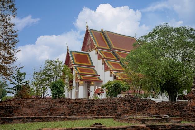 Capela tailandesa de wihan phra mongkol bophit (salão de imagens) perto do templo wat phra si sanphet no parque histórico de ayutthaya, tailândia, parede de tijolos velha com templo atrás