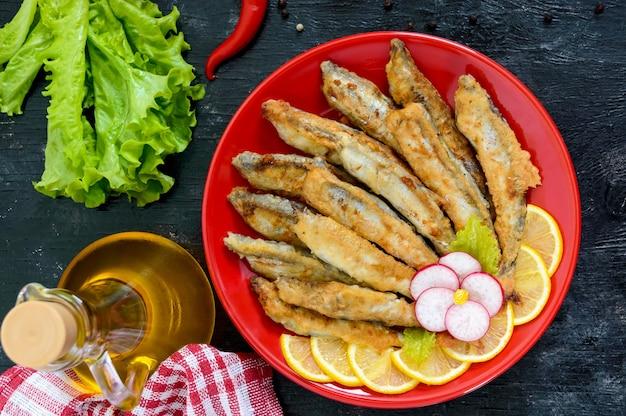 Capelim frito com limão em uma placa vermelha em um fundo preto de madeira. um prato de peixinhos de mar. vista do topo. postura plana