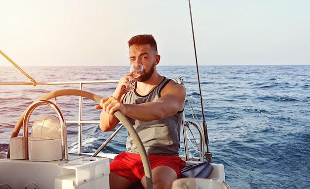 Capitão homem iatismo com copo de vinho.
