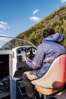 Capitão no leme da vista do barco a motor do cockpit. cair. rússia, altai, lago teletskoye