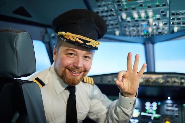 Capitão positivo do avião de passageiros mostrando sinal ok