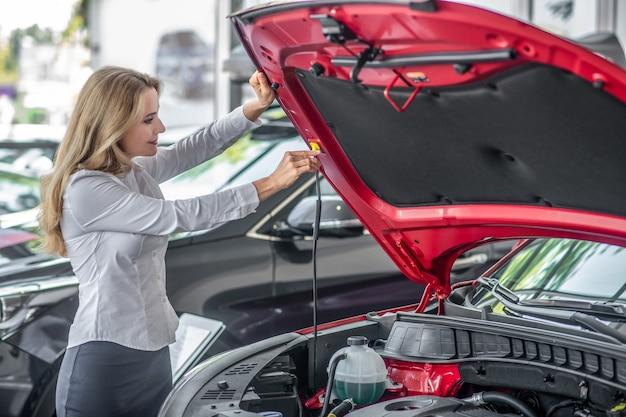 Capô do carro. mulher loira confiante sorridente com blusa branca abrindo o capô do carro vermelho novo na concessionária à tarde