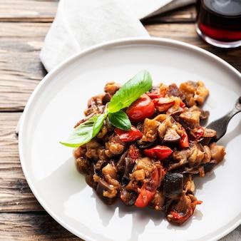 Caponata de prato tradicional de berinjela sicilana na mesa de madeira, foco seletivo e imagem quadrada