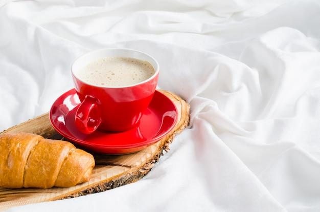 Cappuccino, chocolate e croissant em uma cama.