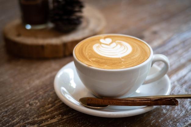 Cappuccino com arte do latte no fundo de madeira. espuma bonita