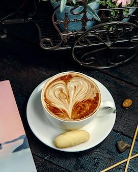 Cappuccino com biscoito em cima da mesa