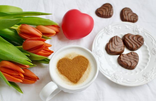 Cappuccino com coração de canela e flores composição tulipas, dia dos namorados conceito de primavera