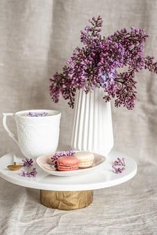 Cappuccino com macaroons na toalha de mesa de linho, flores lilases violetas, conceito matinal
