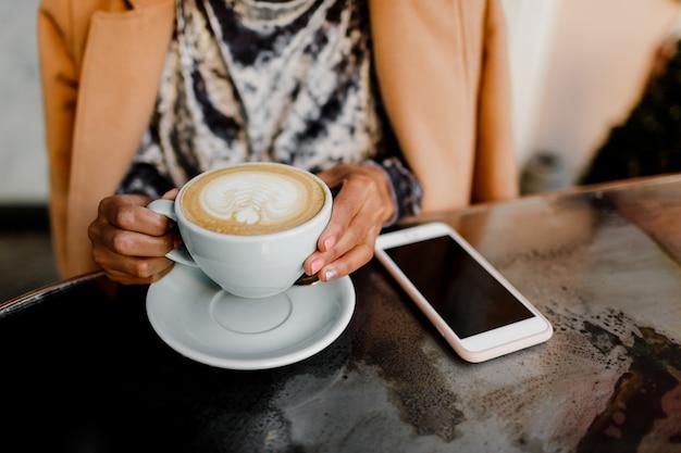 Cappuccino da xícara de café nas mãos da mulher.