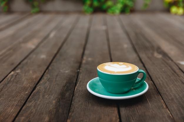 Cappuccino de aroma com espuma de leite exuberante em copo de cor azul