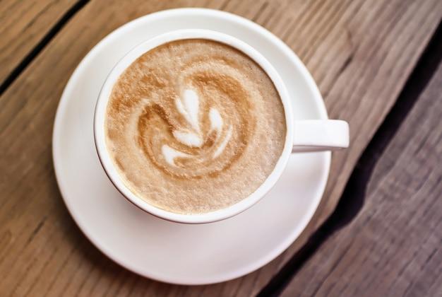 Cappuccino de arte no copo branco na superfície de madeira. fotografia da vista superior. a beleza do minimalismo. foto em tons quentes.