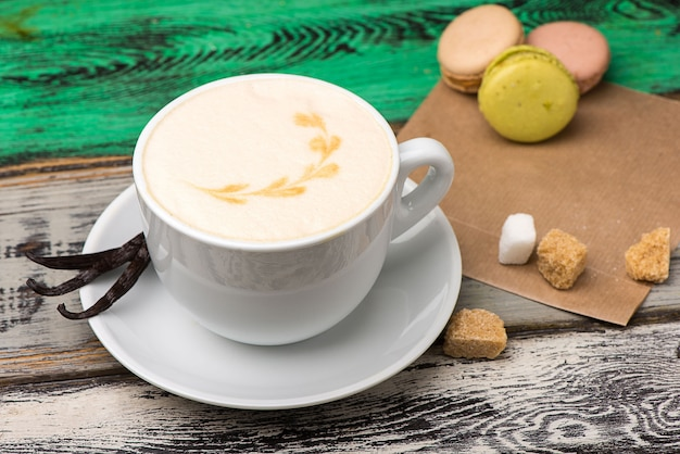 Cappuccino de baunilha em um copo branco com açúcar e biscoitos na mesa de madeira