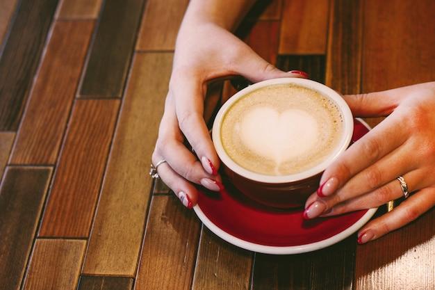 Cappuccino de café com coração de espuma nas mãos de mulher com linda