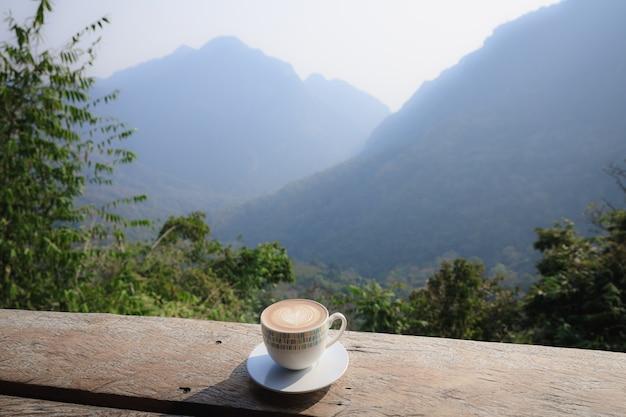 Cappuccino de café quente em copo branco em terraço de madeira com bela vista panorâmica da natureza