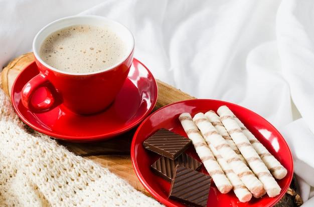 Cappuccino e chocolate em uma cama com manta.
