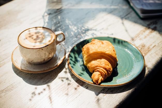 Cappuccino e croissant estão na mesa do café. o sol da manhã cai sobre a mesa, lindas sombras aparecem. delicioso café da manhã.