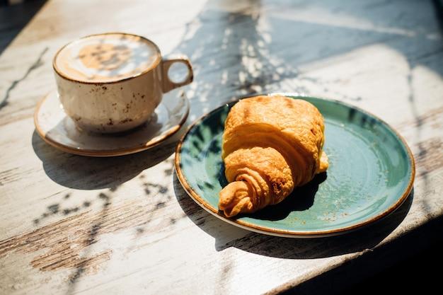 Cappuccino e croissant estão na mesa do café. o sol da manhã cai sobre a mesa, lindas sombras aparecem.
