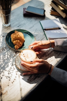 Cappuccino e croissant na mesa do café. o sol da manhã incide sobre a mesa, lindas sombras aparecem. delicioso café da manhã. as mãos das mulheres seguram uma xícara de café.