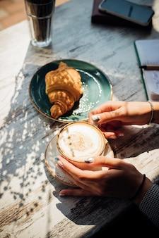 Cappuccino e croissant na mesa do café. o sol da manhã incide sobre a mesa, lindas sombras aparecem.