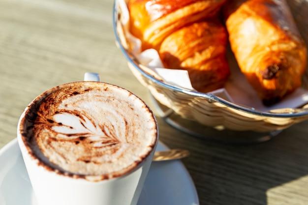Cappuccino e croissants frescos em uma mesa em um café de rua em um dia ensolarado. fechar-se.