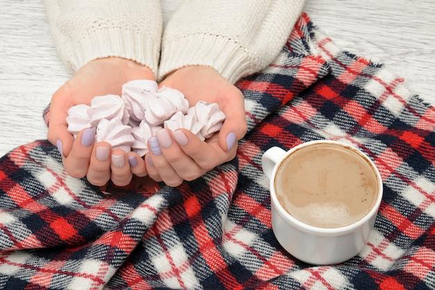 Cappuccino e merengue nas mãos femininas, xadrez xadrez. conceito elegante