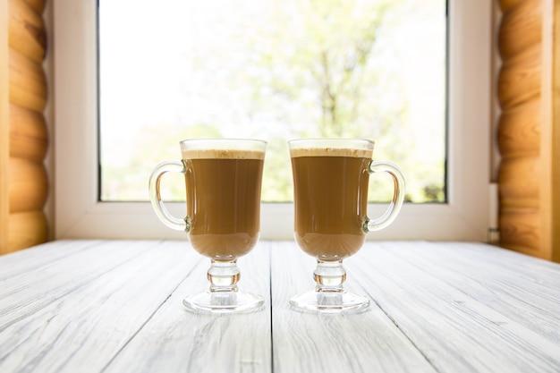 Cappuccino em copo de vidro contra janela