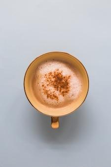 Cappuccino em um copo com chocolate em pó no fundo branco