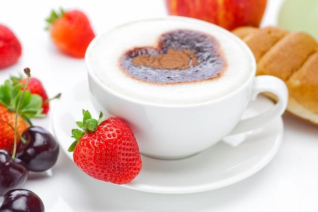 Cappuccino em um copo em forma de corações, cereja, croissant e